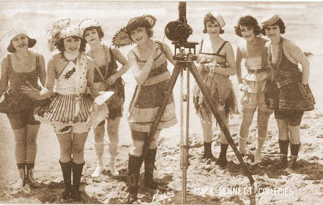 arcade-card-mack-sennett-comedies-7-women-in-bathing-suits-on-beach-with-camera-1920s